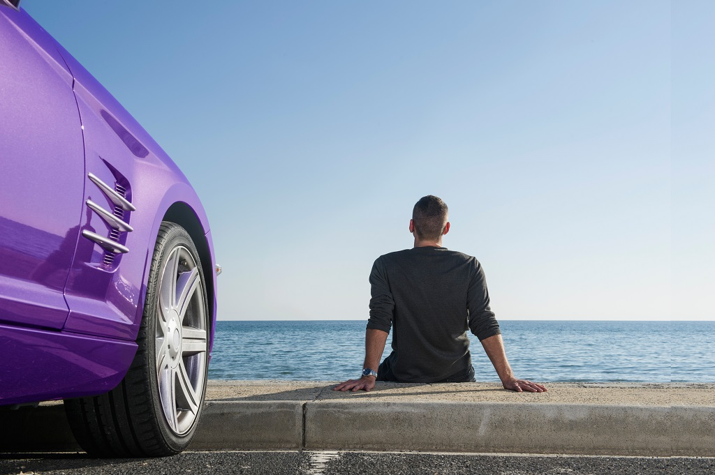 Man relaxing by car on beach