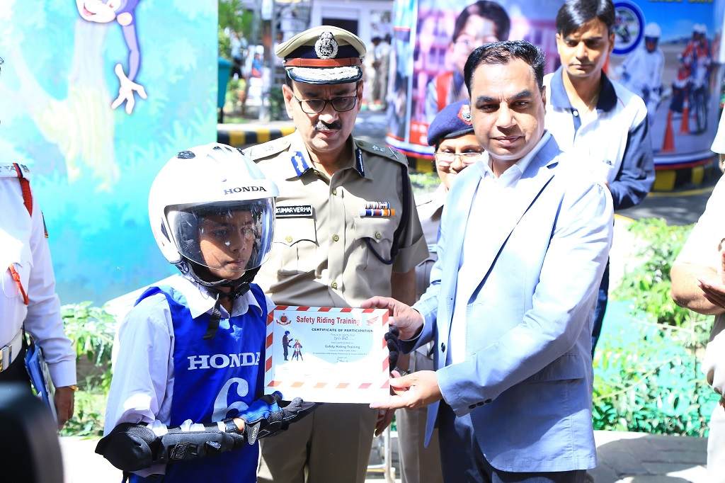 Mr. Y.S Guleria, Senior VP, Sales & Marketing, HMSI rewarding kids at Honda's Road Safety Summer Camp with Mr. Alok Kumar Verma, Commissioner of Police, Delhi